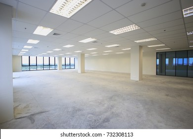 Interior empty office light room with white wallpaper without furniture in a new building renovation or under construction.Glass doors and Windows.