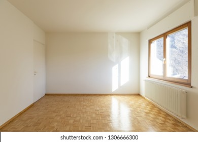 Interior of a empty room with just a window. We can see a small radiator and the floor with wood