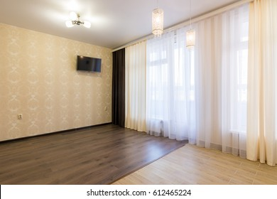 The interior of an empty room in the newly renovated, with a large curtained window