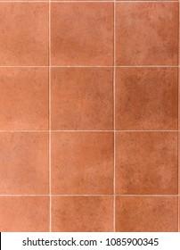 Interior or exterior bathroom or kitchen square ceramic tiles. Image of interior flooring with red orange pavement slabs.