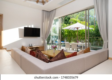 Interior and exterior design of living room with pool view in luxury pool villa feature television, sofa, couch, cushion, TV console, curtain and sliding door and garden