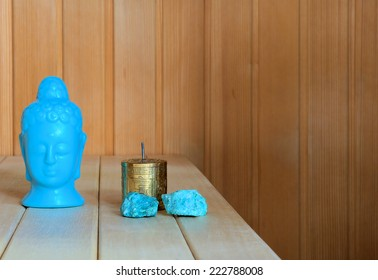 Interior of a finnish sauna with a still life of buddha, a small mongolian meditation wheel and blue stones. It leaves room for typing.
