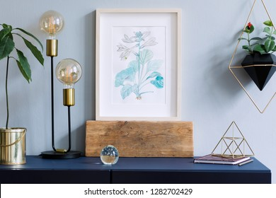 Interior floral poster mock up with vertical wooden frame, table lamp, avocado plant, accessories and hanging plants in geometric pot on the grey wall background. Concept with navy blue shelf.