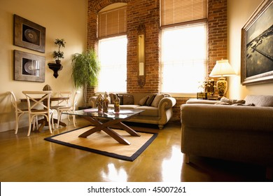 Interior of furnished living room with large windows and brick wall. Horizontal shot.