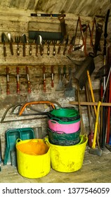 Interior of a garden shed, with racked and stored tools and colourful plastic flexi tub trugs. With saws, trowels, forks, hoes and rakes. Portrait.