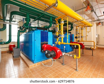 Interior gas boiler house with a lot of industrial boilers, pipes and pumps.