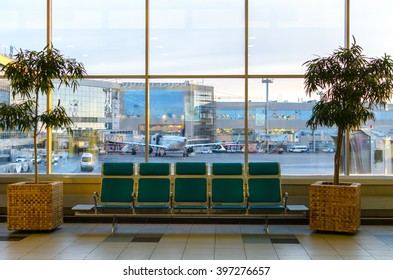 the interior with green sits, big window, trees of the pulkovo airport in saint-petersburg, russia.