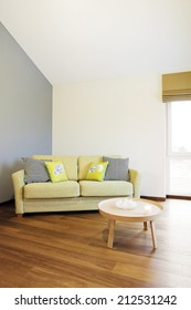 Interior - green sofa in front of blank wall in a bright room