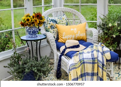 Interior of Greenhouse with white wicker chaise lounge, blue and yellow pillows and throw blanket, blue delft pitcher with yellow sunflowers, stenciled floor and green plants