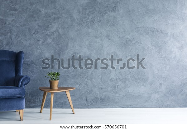 Interior with grey wall blue armchair and wood side table
