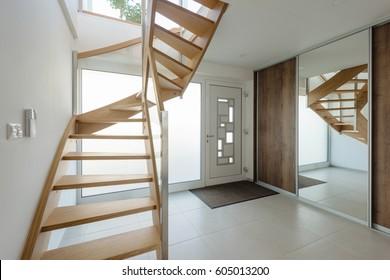 Interior of hallway with entrance door and wooden stairway
