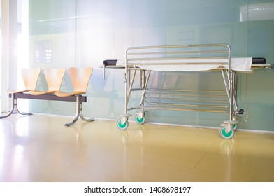 Interior of healthcare center hallway. Modern and gleaming environment with stretcher and wooden waiting chairs