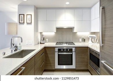 Interior of high-rise apartment building: modern white kitchen with grey wood paneling.