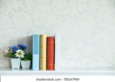 Interior home decor with flowers and books on shelf