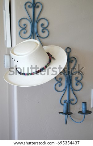 fc21c9db56d Interior home photo of straw cowboy hat hanging on a pair of chippy  cornflower blue painted