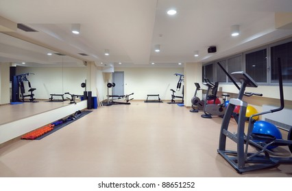 Interior of a hotel fitness club equipped with fitness devices.