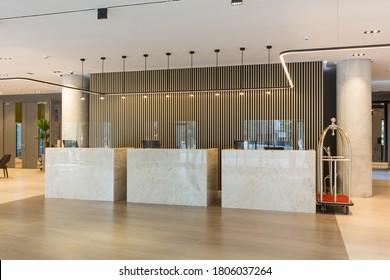 Interior de un vestíbulo de hotel con mostradores de recepción con centelleadores transparentes de plexiglás y estornudos claros