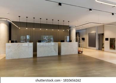 Interior de un vestíbulo de hotel con mostradores de recepción con vigilantes transparentes