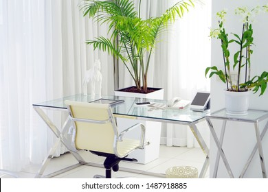 Interior of the hotel's living room. Beautiful writing desk. White interior concept of the apartment. Modern interior of the office in a luxury villa. White color, large window.