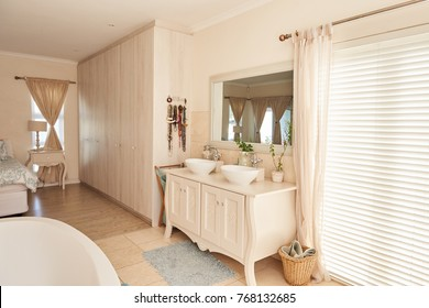 Interior image of stylish contemporary bathroom with basins, a toilet and bath in a open space residential home, with bedroom in background
