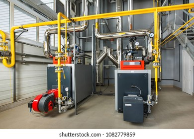The interior of an industrial boiler house with a multitude of pipes, boilers and sensors.