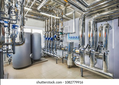 The interior of an industrial boiler house with a multitude of pipes, barrels and sensors.