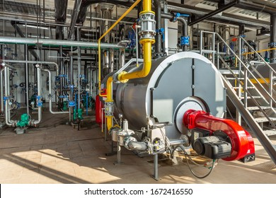 Interior of an industrial boiler room with boilers, many pipes, valves and sensors.