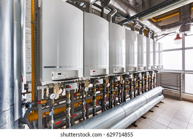 Interior of industrial, gas boiler house with a lot of boilers and equipment.