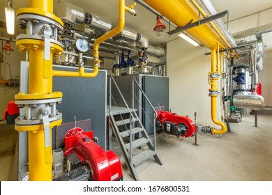 interior of an industrial gas boiler room with boilers and pipelines.