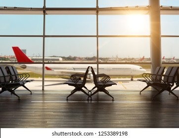 Interior inside the airport terminal with chairs in waiting departure area and view of airplane passing outside.