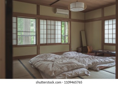 interior inside the bedroom of old style Japanese Ryokan room with white futon mattress on the tatami mat.