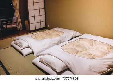 interior inside the bedroom of old style Japanese Ryokan room with white futon mattress on the tatami mat