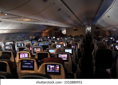 Interior of a jet airplane on a long international flight with TV screens on the back of seats over the Atlantic Ocean - June 23, 2019