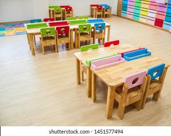 Interior of kindergarten classroom consist desks and chairs.