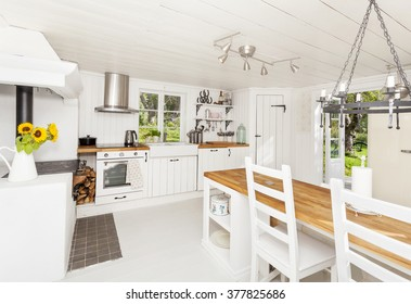 interior of a kitchen in the countryside with white wooden floor and ceiling