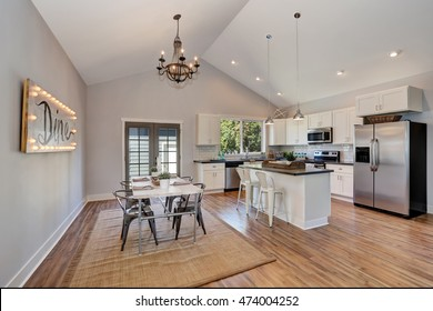 Interior of kitchen and dining room with high vaulted ceiling. white kitchen cabinetry and steel appliances. Northwest, USA