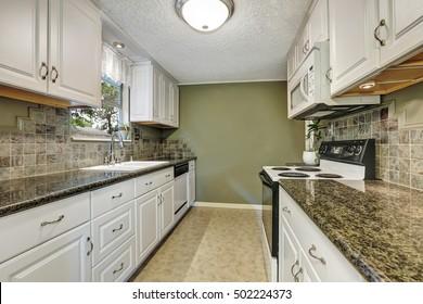 Interior of kitchen room with white cabinets, granite tops, natural stone back splash tile trim and linoleum floor. Northwest, USA