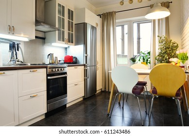 Interior of the kitchen in Scandinavian style with white furniture and a dining table