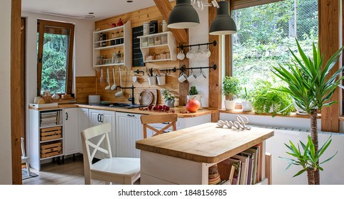 Interior of kitchen in vintage rustic style with wooden furniture in a cottage. Bright indoors in a cozy kitchen with window and plant.