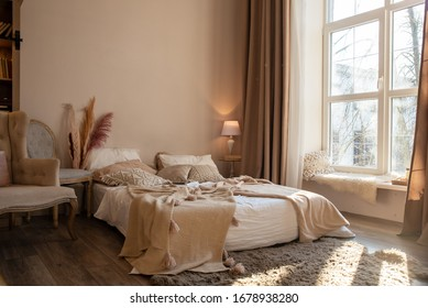 Interior of a large bedroom. Lots of light from a large window, a comfortable, soft bed. Thoughtful style