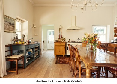 Interior of a large country style kitchen in a residental home with a wooden dining table and appliances