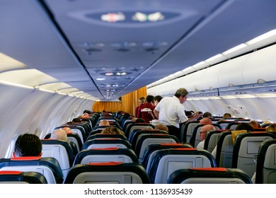 Interior of large passengers airplane with people on seats and stewardess and steward in uniform walking the aisle