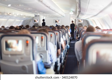 Interior of large passengers airplane with people on seats and stewardess in uniform walking the aisle.
