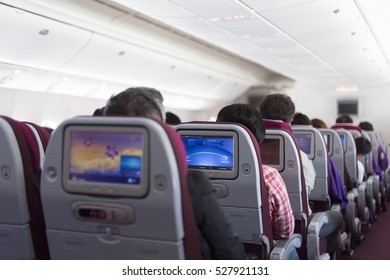 Interior of large passengers airplane with people on seats.