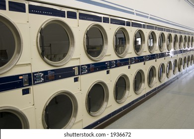 The interior of a laundromat -- a long row of commercial driers