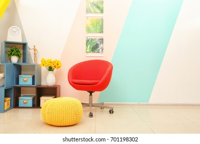 Interior of light modern room with comfortable rolling armchair, shelves and ottoman