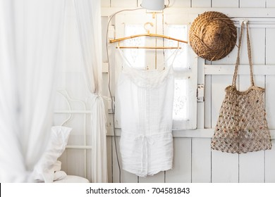 Interior of light modern wooden house inside, vintage window with shutters and decorative curtains. Straw hat, hanging dress and handmade wicker bag. Rustic and village style