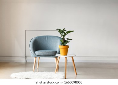 Interior of light room with armchair and table with houseplant