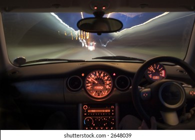 Interior of lit up dashboard of car traveling at speed at night. Orange dials and light blurs