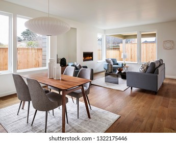 Interior living area with couches, chairs and a dining table with a fireplace